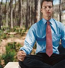 Well-Dressed Businessman Sits in a Forest, Meditating in the Lotus Position