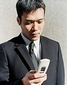 Young Businessman Dialling a Mobile Phone
