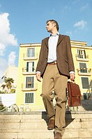 Well-Dressed Man Carrying a Briefcase Descends Steps in an Urban Setting