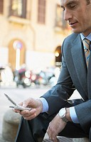 Businessman Sits in an Urban Setting Texting on His Mobile Phone