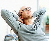 Man Sits With His Hands Behind His Head, Looking Up in Inspiration