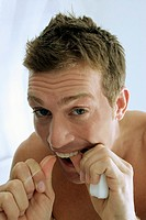 A man flossing his teeth