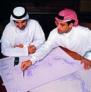 Arab businesspeople discussing architectural sketch