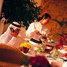 Waitress serving lunch to Arab businessmen