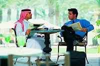 Arab businessmen reading newspaper