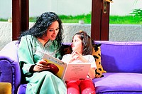 Mother and daughter reading in a book