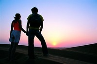 Western tourist couple watching sunset in the desert, United Arab Emirates