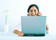 Woman sitting with laptop, talking on phone and laughing