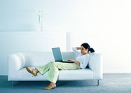 Woman lounging on sofa and using laptop