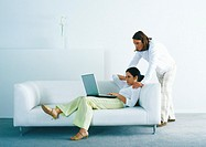 Woman lounging on sofa and using laptop, man standing, looking over woman's shoulder