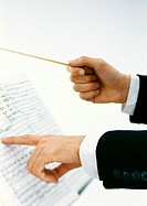 Conductor's hands holding baton and pointing to sheet music