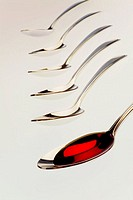 Six spoons, one with red liquid