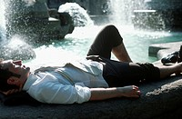 Geschaeftsmann liegt auf einem Brunnenrand - Erholung , Businessman lying on the Brim of a Fountain - Recreation ,  fully-released