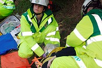 Emergency treatment. Paramedics treating a woman with a suspected neck injury. A rigid cervical collar (neck brace) has been placed around the woman´s...