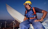 Wind farm. Engineer sitting 60 metres above the ground on the top of a wind turbine. Wind turbines are used to generate electricity from the winds tha...
