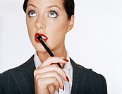 Businesswoman Holding a Pen Against Her Lips and Looking Up