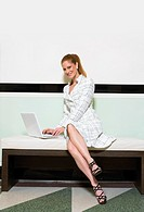 Portrait of a Well-Dressed Businesswoman Sitting on a Bench With a Laptop