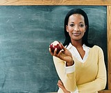 Portrait of a Teacher Standing in Front of a Blackboard Eating an Apple
