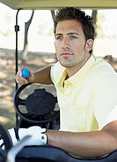 Young Man Sitting in a Golf Buggy Holding a Golf Ball