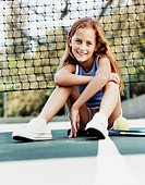 Portrait of a Young Girl Sitting on a Tennis Court by the Net