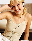 Young Woman in a Vest Listens to Music With Headphones
