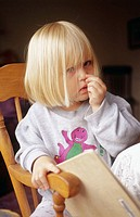 Little girl picks nose in rocking chair