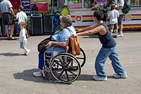 Grandson pushes grandmother in a wheel chair