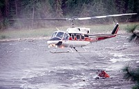 Helicopter pulls water from the Clearwater River to drop on forest fire. Idaho, USA