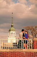 Couple shares a private moment with spire of library in background