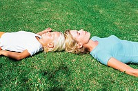 Mother and daughter asleep on lawn