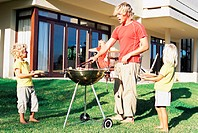 Father doing a barbecue for his family