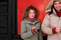 Couple in winter clothes with warm drinks (thumbnail)