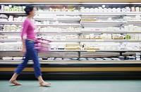 Blurry woman walking in grocery store