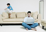 Man working on laptop while son jumps on couch