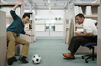 Two businessmen playing soccer in office