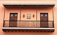 Puerto Rico, San Juan. Wooden second floor balcony, two doors, Virgin Mary and Jesus painting on wall, exterior