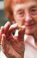 Senior woman holding pill