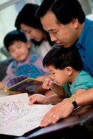 Parents watching their two sons coloring with crayons (thumbnail)