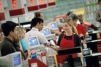Customers standing at a checkout counter in a supermarket