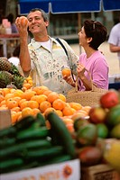Mature couple picking oranges from shop in a market