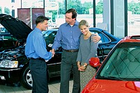 Mid adult couple talking to a car salesman in a car showroom