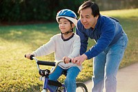 Father helping his son ride a bicycle