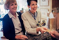 Two mature women at a store counter