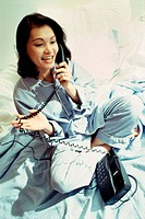 High angle view of a young woman sitting on a bed talking on a telephone