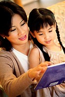 Mother reading a storybook with her daughter
