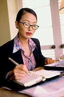 Businesswoman writing in a planner