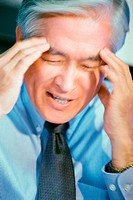 Close-up of a businessman holding his head
