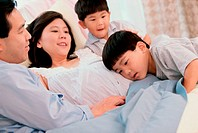 Son with his head against his pregnant mother´s abdomen