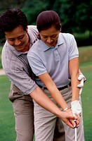 Mid adult man teaching a mid adult woman golf