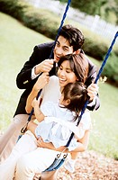 Close-up of parents playing with their daughter on a swing